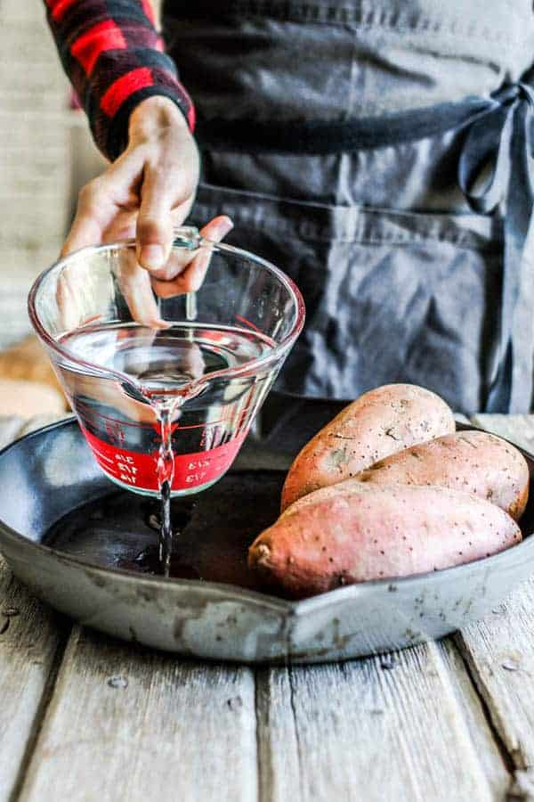 sweet potatoes in a skillet, water is being poured into the skillet.