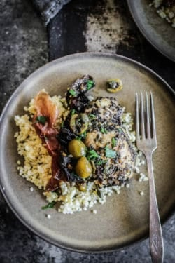 A plate with Quick and Easy Sheet Pan Chicken Marbella over cooked millet with a crispy ribbon of proscuitto