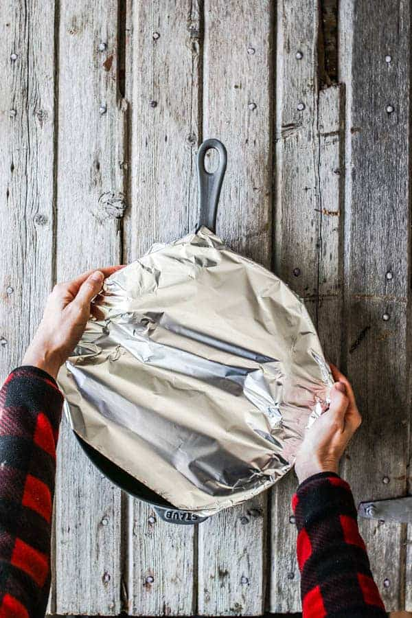 a woman covering a skillet with aluminum foil