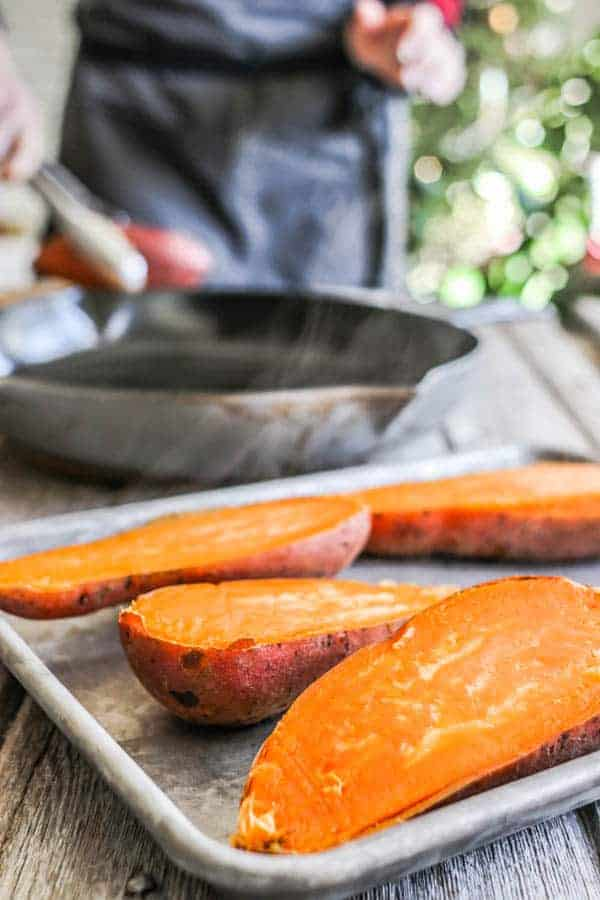 halved sweet potatoes on a baking sheet with a woman standing in front of a hot skillet on the background.