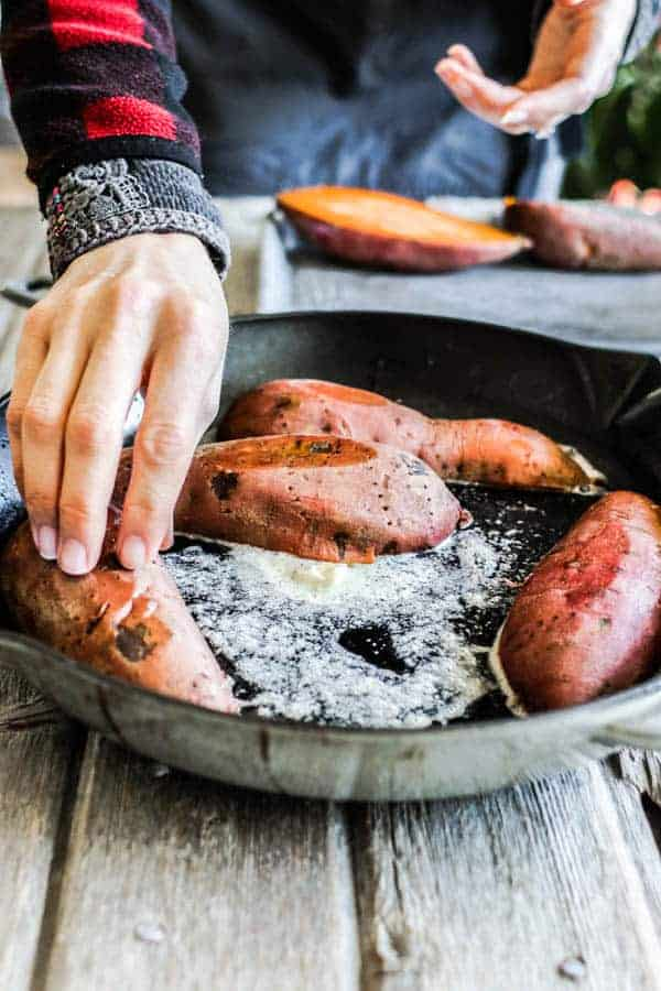 A woman placing halved sweet potatoes slice side down in a skillet of melted butter.