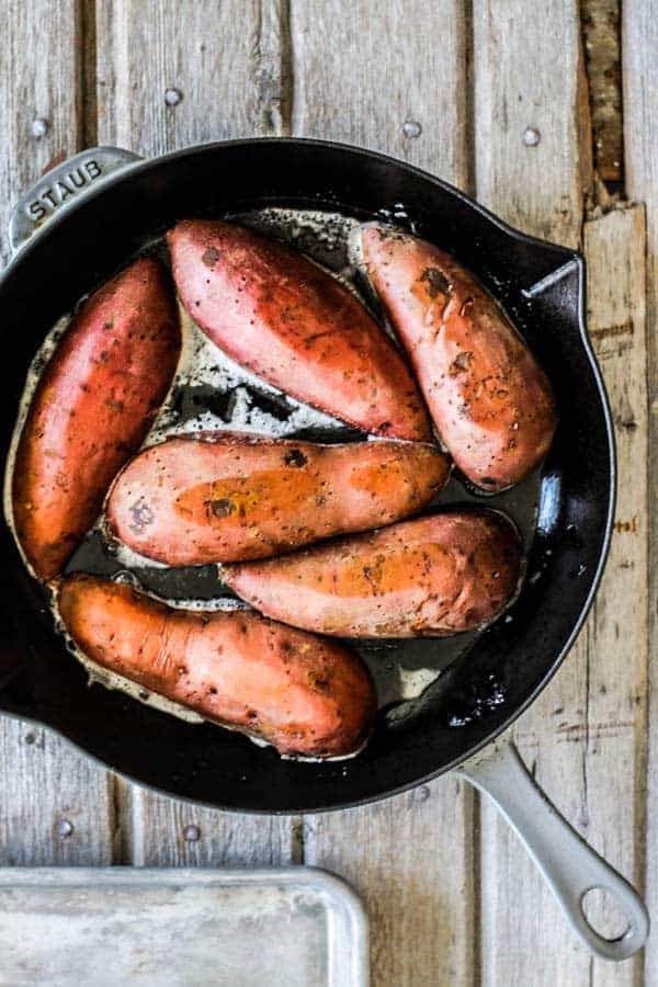 Sweet potatoes nestled in a skillet of melted butter to be roasted in the oven.