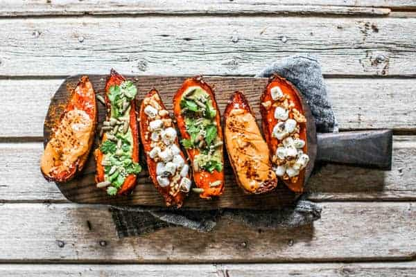 A wood serving board lined with 6 roasted sweet potato halves all topped different ways.