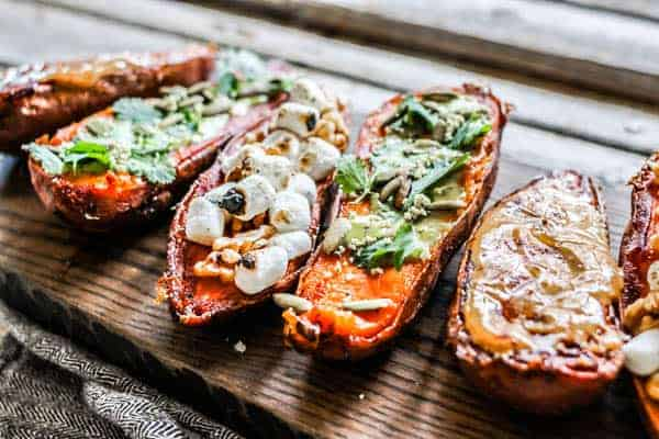 A wood serving board lined with sweet potatoes topped with varying sweet and savory toppings.