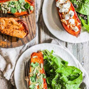 A platter of halved sweet potatoes topped with varying sweet and savory toppings. Two sweet potato halves are plated with side salads