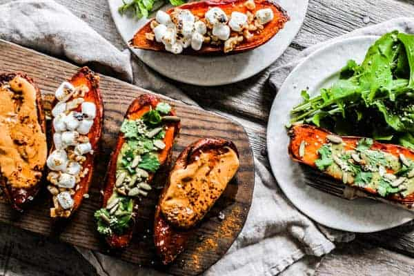 A platter of roasted sweet potato halves with toppings