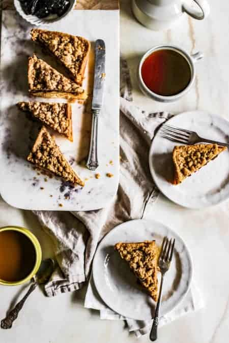 Slices of Weekend Coffee Cake Crumble on a serving platter with cups of coffee and a small bowl of dried fruit