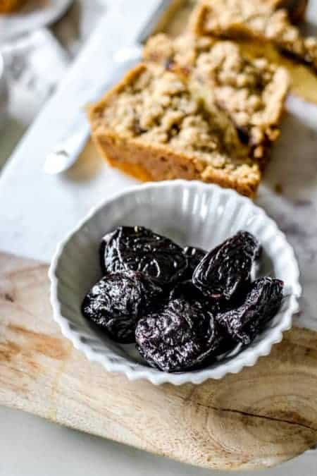 A bowl of prunes next to slices of weekend coffee cake crumble