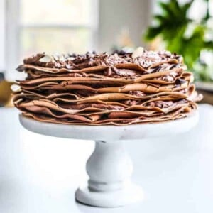 A chocolate crepe cake on a white cake stand