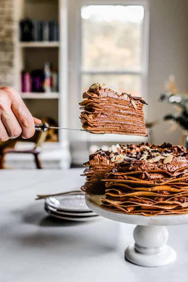 A slice of crepe cake being lifted up from teh cake on a cake server