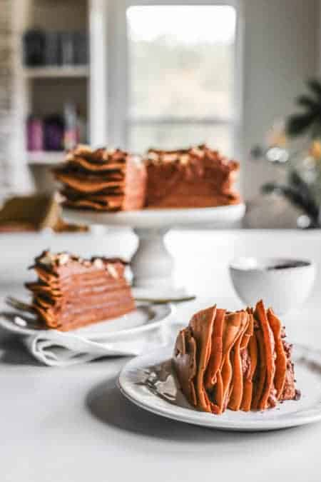 A Chocolate Crepe Cake on a cake stand with 2 slices taken out. One is turned on its side on a dessert plate while sth mother is right side up on a desert plate.