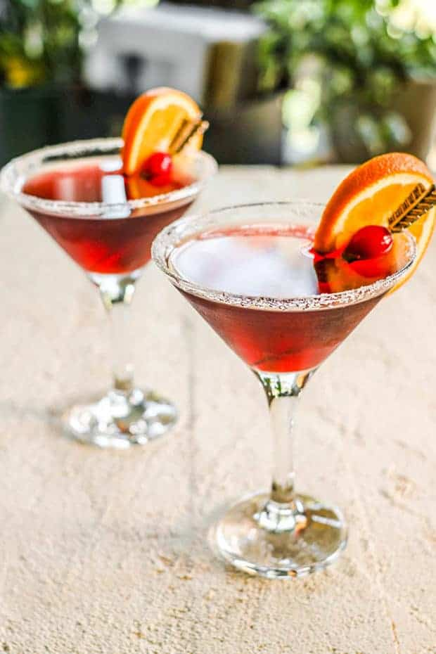 Two Super Antioxidant Martini on a table top with range wedge and cranberry garnish