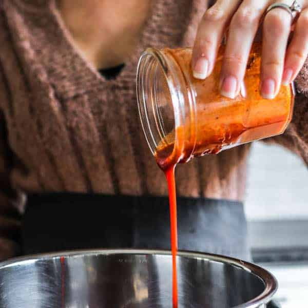 A close up of red enchilada sauce being poured