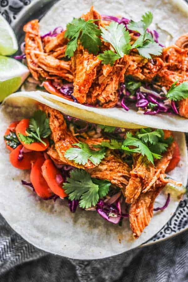 Close up of Shredded Instant Pot Mexican Chicken recipe piled on a taco
