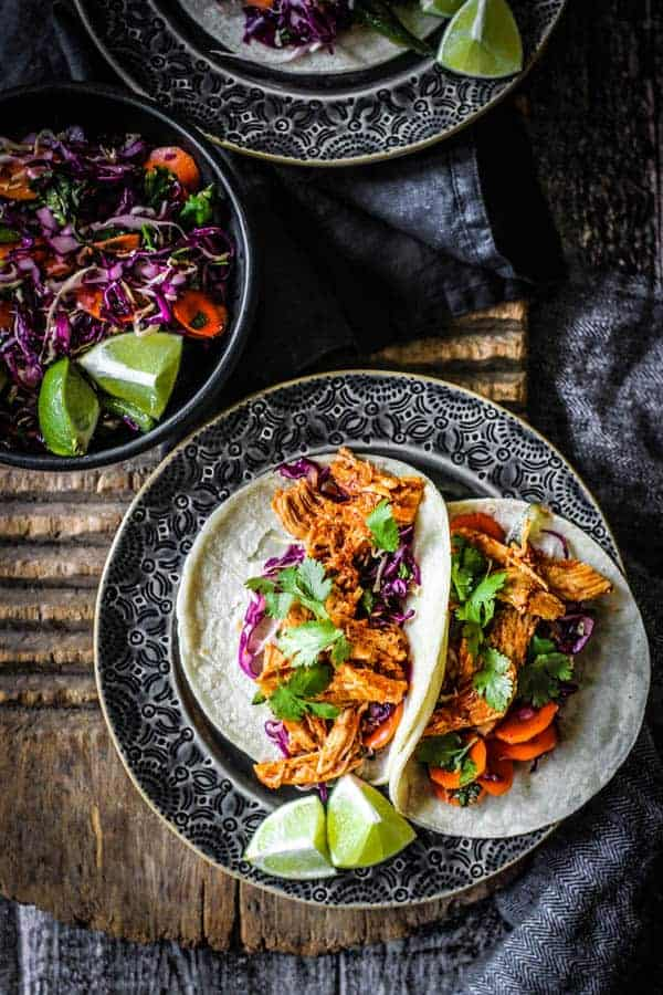 Two Shredded Instant Pot Mexican Chicken recipe tacos are on a plate with lime wedges next to a bowl of colorful spicy slaw