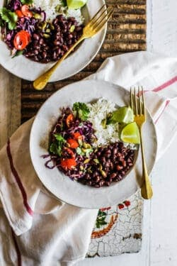 Two vegetarian burrito bowls with black beans, rice, spicy colorful slaw, and lime wedges