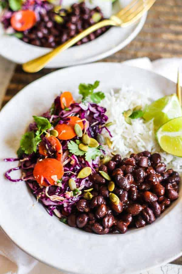 A bowl of black beans with rice, spicy colorful slaw, cilantro and lime wedges.