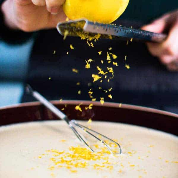A lemon being zested over the batter for the recipe for french toast