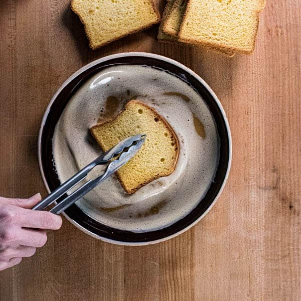 A piece of brioche being dipped into the custard for the perfect french toast recipe