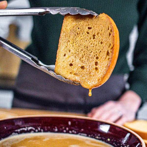 A slice of brioche that has been dunked in the French toast custard and the excess is running off while it is being held in mid air by tongs.