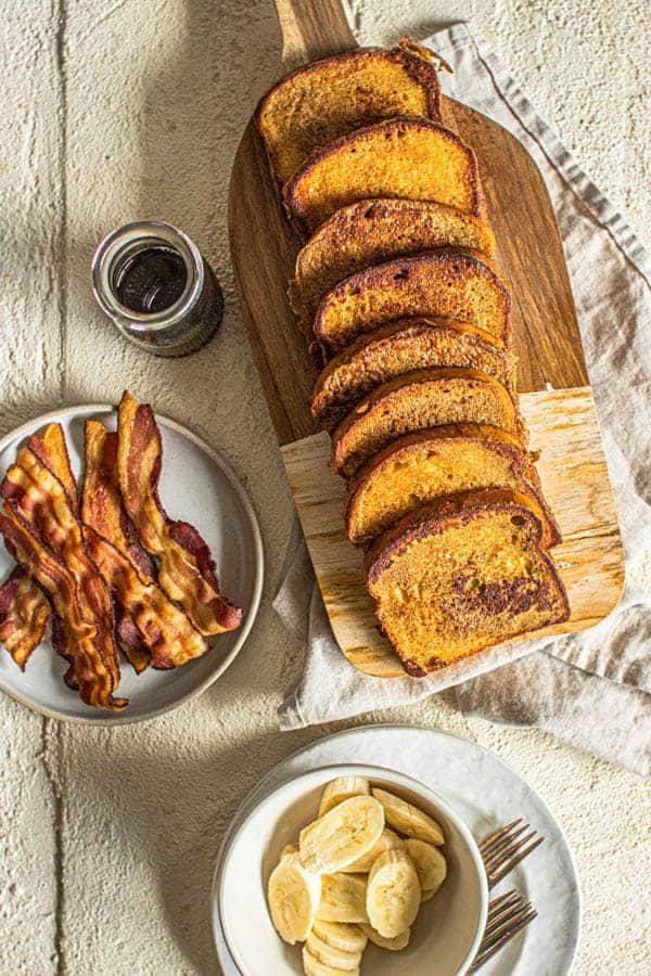 French toast, bacon, maple syrup, and fruit on a table