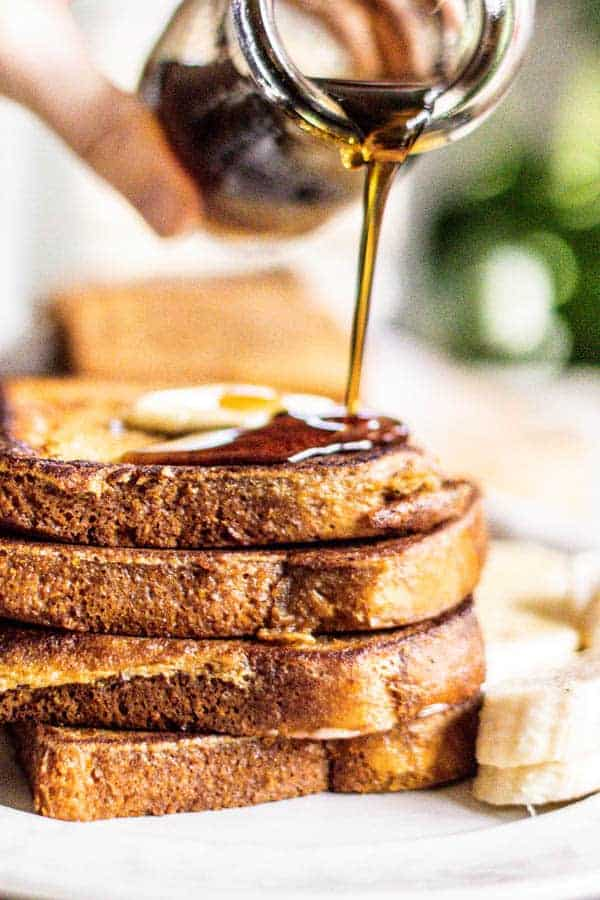 A stack of French toast up close with butter on top and maple syrup being poured over it.