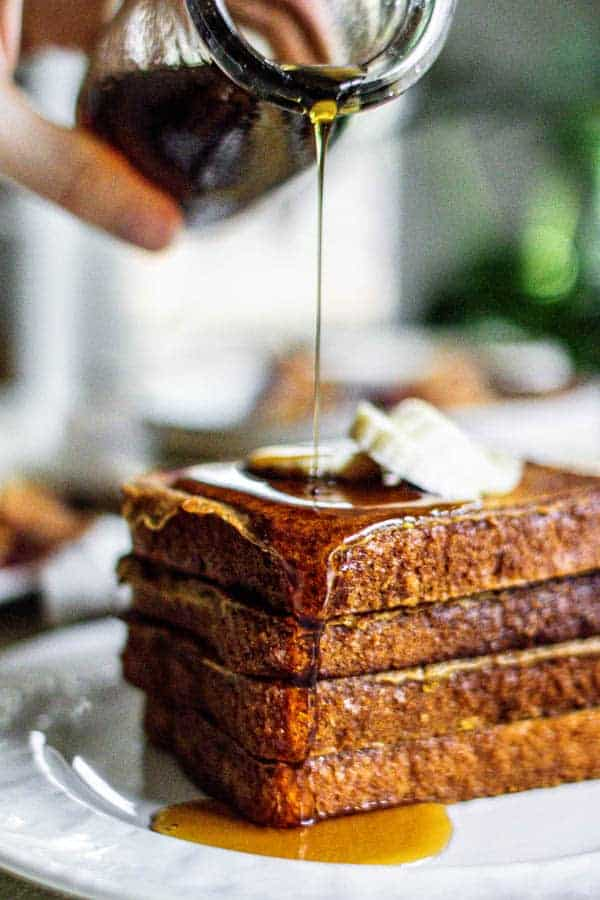 A stack of French toast being drizzled with warm maple syrup