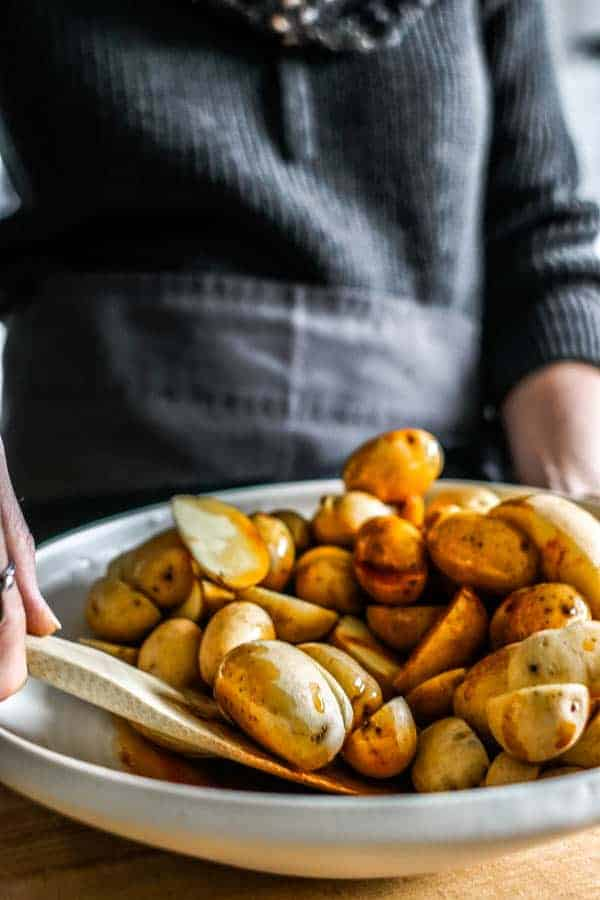 A woman stirring the spices and potatoes together to male crispy oven roasted potatoes