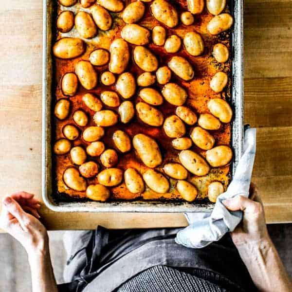 Potato halves cut side down on a sheet pan