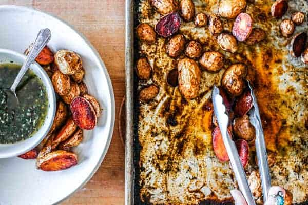 A sheet pan sits on a counter with oven roasted potatoes on it and a pair of tongs. There is a bowl next to the sheet pan that has a few scoops of the oven roasted potatoes in it and a smaller bowl that has a green dipping sauce