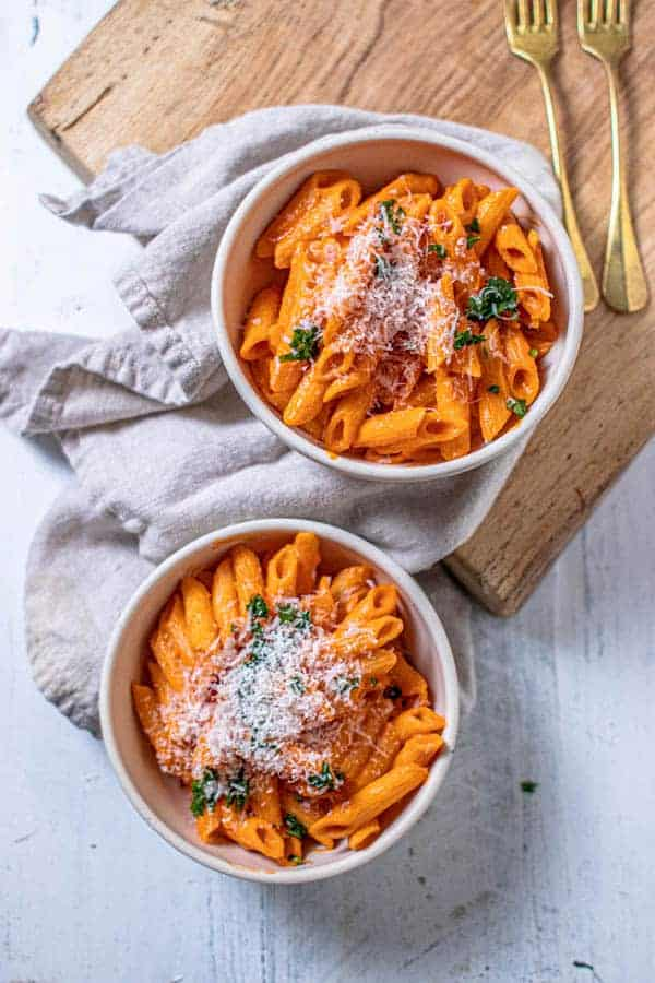 Two bowls of pasta tossed in 5-ingredient marinara sauce recipe and topped with chopped parsley and shredded Parmesan