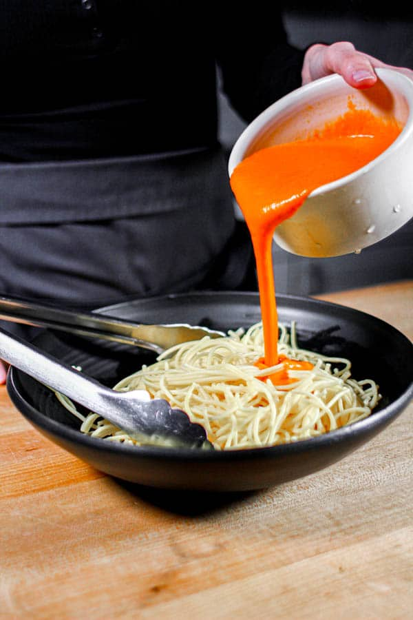 Marinara sauce being poured over cooked pasta