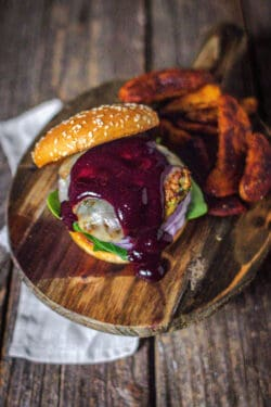 Our turkey burger recipe showcased on a bun with spinach, red onion, and jalapeño jack cheese. There is Blueberry Jalapeño Sauce dripping down the turkey burger.
