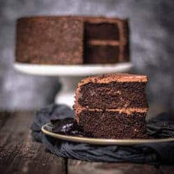 A 2-layer chocolate cake with chocolate icing, decorated with chocolate sprinkles is in the background while a slice of the cake is plated in front with a few Californian prunes on the plate.