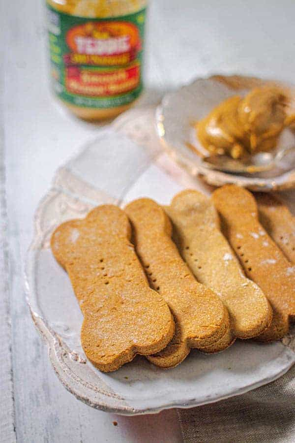 Homemade peanut butter dog treats shaped like bones on a plate next to a bowl of peanut butter.