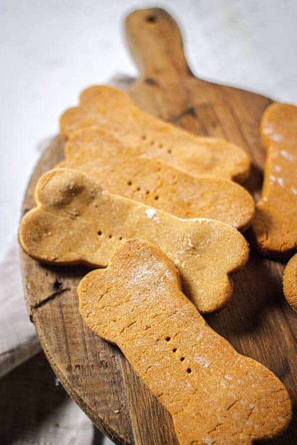 Peanut butter dog treats shaped like bones on a wooden tray
