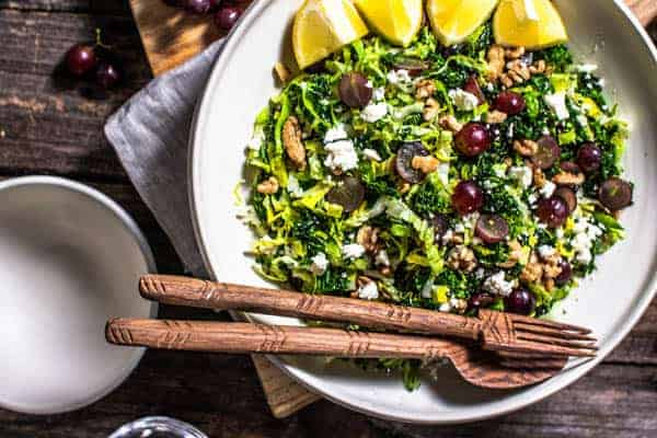 A close up of a Kale Salad recipe with feta, dill, walnuts, and red grapes