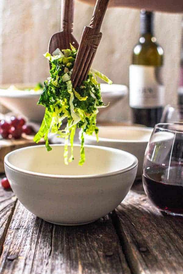 Kale salad being served into a salad bowl. A bottle of GEN5 Zinfandel is in the background