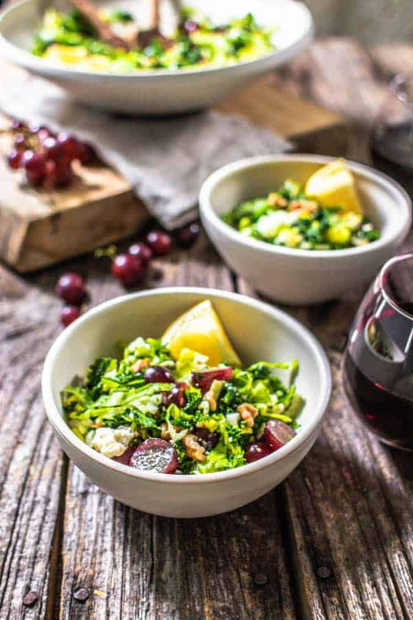 Kale Salad with Red Grapes, Walnuts, and Feta in 2 bowls with glasses of red wine ready to serve