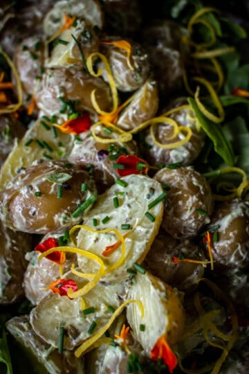 A close up of green goddess potato salad topped with edible flowers and fresh herbs.