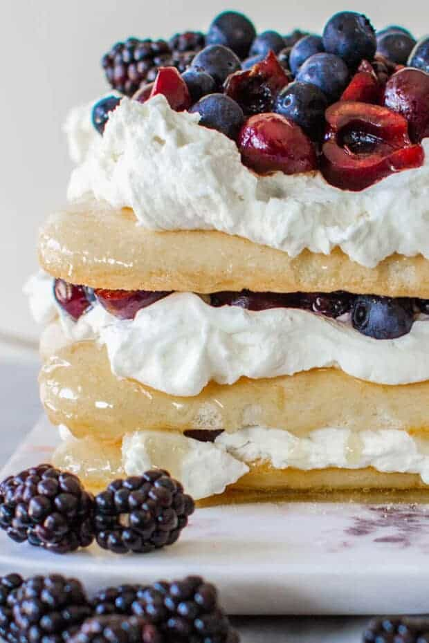 This red, white, and blue dessert cake from the side view. Stacked citrus-caramel soaked Lady Fingers, layered with with mascarpone whipped cream and fresh cherries, blackberries and blueberries