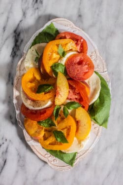 A plate of Caprese Salad with Peaches and yellow and red Heirloom Tomatoes.