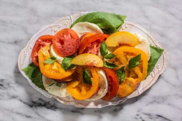 A plate of Caprese Salad with Peaches and Heirloom Tomatoes.