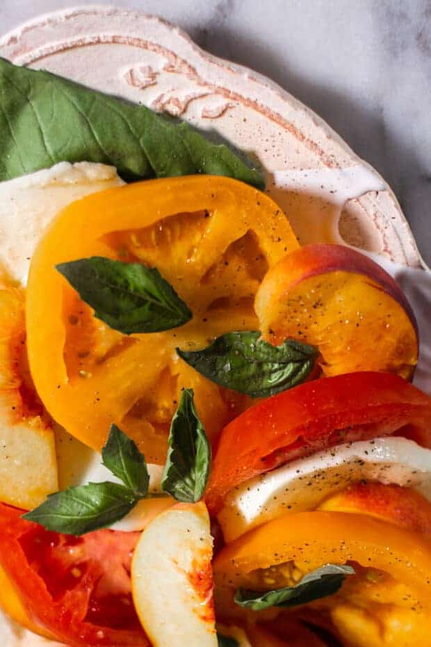 A plate of Caprese Salad with Peaches and yellow and red Heirloom Tomatoes. close up.