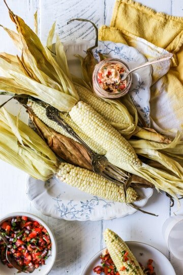 How to Cook Corn on the Cob in the Oven in the husk. The corn is served on a platter.