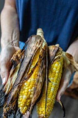 A woman holding grilled corn in the husk after demonstrating how to grill corn in the husk.