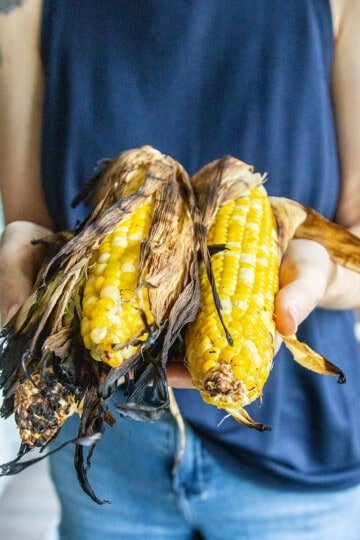 Corn that was grilled in teh husk being held up for the camera.