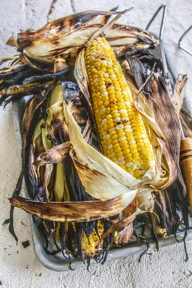 A sheet pan of grilled corn in the husk