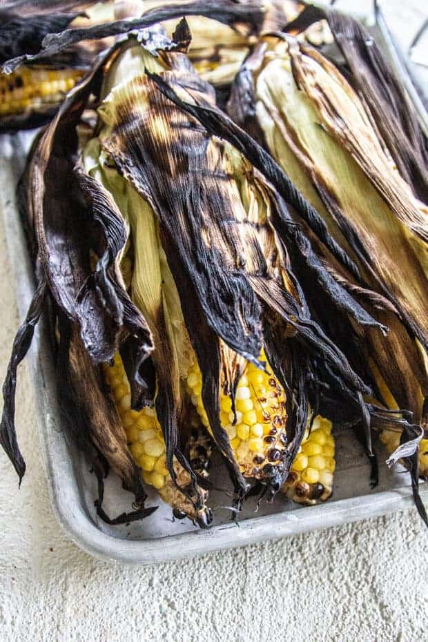 Corn that was grilled in the husk so that the husk is charred but the kernels are not.